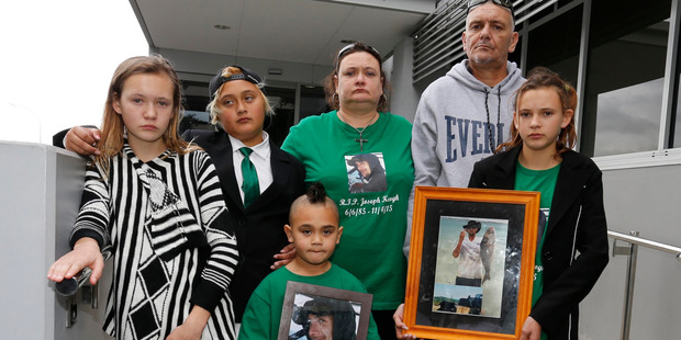 Joseph Rowland Keogh's family with a photo of him outside court after the sentencing. From left, sister Angel-Aroha, sons Vince Patrick and Kupe, parents Morag and Rowland, and sister Jacinta.