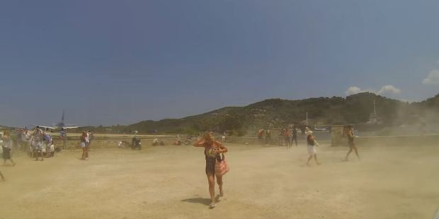 Tourists ran for cover as the jet sent clouds of sand billowing. Photo / YouTube, Cargospotter