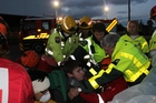 In the dark on Saturday night, Dannevirke volunteer firefighters, St John personnel and Red Cross crews work to free an accident victim from a car crash, using the St John chair lifter.
