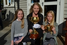 Yana Chaplow (left), Tracey Andersen and Vaya Chaplow get up close and personal with the 2016 and 1916 Melbourne Cups on Saturday.