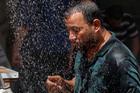 An Iraqi man cools off the summer heat by using an open air shower in Baghdad. Photo / AP