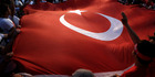 Protesters wave a large Turkish flag during an anti coup rally in Taksim square in Istanbul. Photo / AP