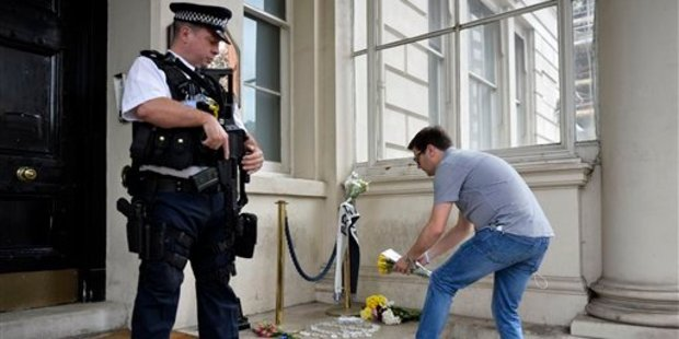 An armed police officer watches as a man lays flowers at the steps of the French Embassy in London, after a truck plowed through revelers in Nice, France. Photo / AP