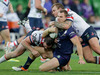 Cheyse Blair of the Melbourne Storm gets tackled by a pair of Sydney Roosters players at AAMI Park in Melbourne last night. Photo / Getty Images