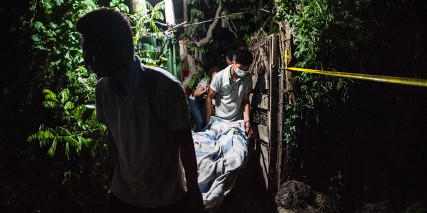 Forensic workers take out the body of an alleged drug dealer killed in a shootout with police during a drug raid. Photo / Getty Images