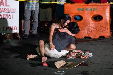 MANILA, PHILIPPINES - JULY 23: A woman clutches her dead husband in grief after armed assailants in a motorcycle shot him in a main thoroughfare on July 23, 2016 in Manila, Philippines. The victim wa