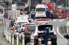 Police officers stand by with ambulances and fire trucks on a street near a centre for the handicapped where a number of people were killed and dozens injured in a knife attack. Photo / AP