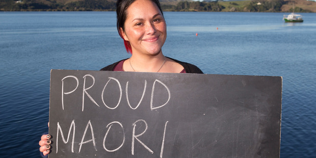 Shannon Baker in Mangonui, with a chalkboard message on what it means to be a New Zealander. Photo / Mark Mitchell