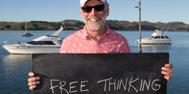 Wayne Brown in Mangonui, with a chalkboard message on what it means to be a New Zealander. Photo / Mark Mitchell