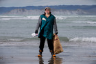 Tina Ngata on Kaiti Beach, Gisborne, with the rubbish she has picked up on the sand. Photo / Alan Gibson