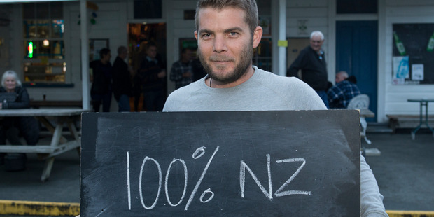 Paul Norris, 29, of Puhoi with a chalkboard message on what it means to be a New Zealander. Photo / Mark Mitchell