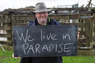 Scott McInnes, 48, in Dargaville with a chalkboard message on what it means to be a New Zealander. Photo / Mark Mitchell