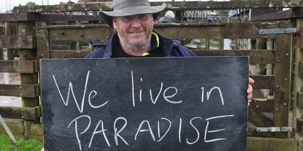 Loading Scott McInnes, 48, in Dargaville with a chalkboard message on what it means to be a New Zealander. Photo / Mark Mitchell