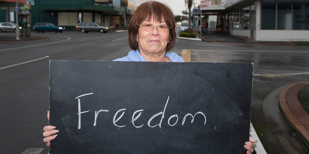 Lily Rihana, 69, in Kaikohe with a chalkboard message on what it means to be a New Zealander. Photo / Mark Mitchell