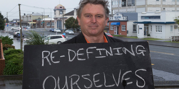 Vernon Woods, 59, in Dargaville with a chalkboard message on what it means to be a New Zealander. Photo / Mark Mitchell