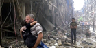 A man carries a child after airstrikes hit Aleppo in Syria. Photo / AP