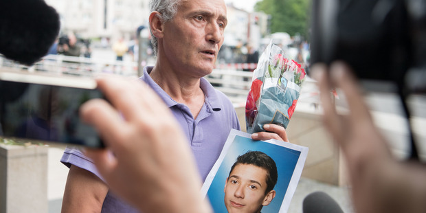 The father of a victim shows a picture of his son near the Olympia shopping centre where a shooting took place leaving ten people dead. Photo / AP