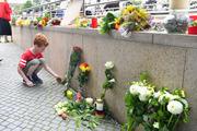 A little boy puts down flowers near a mall where a shooting took place. Photo / AP