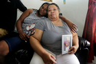 Stephanie White, right, holds a photograph of her son Stef'an Strawder who was killed in the deadly shooting outside the Club Blu, Florida. Photo / AP