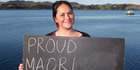 Shannon Baker, 27, in Mangonui, with a chalkboard message on what it means to be a New Zealander. Photo / Mark Mitchell