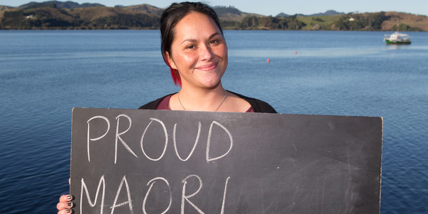 Loading Shannon Baker, 27, in Mangonui, with a chalkboard message on what it means to be a New Zealander. Photo / Mark Mitchell