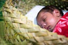 A one-month-old baby in a wahakura. Every year 40 NZ babies die unexpectedly in their sleep, some smothered or suffocated when co-sleeping with parents.