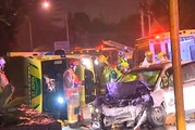 An ambulance has rolled after a speeding car crashed into the emergency vehicle on a major Auckland suburban street this morning. Photo / ONE News