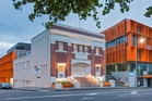 The mixed-use new building acts as a backdrop to the historic Orange Coronation Hall at 145 Newton Rd.