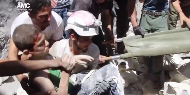 Loading A boy is pulled from the rubble of a building in Aleppo, Syria after a bombing.