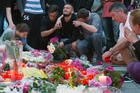 People mourn in Munich after a shooting left nine dead. Authorities say the gunman had no ties to Isis and may have been a depressed loner. Photo / AP