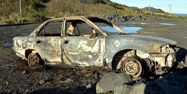 A torched car at Blackhead in Dunedin yesterday is part of a string of cars that have been stolen, then set on fire. Photo / Otago Daily Times