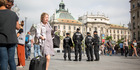 Police officers stand guard as a woman wheels her luggage through Karlsplatz in Munich, Germany. Photo / Bloomberg