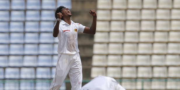 Sri Lanka's bowler Lakshan Sandakan celebrates as Kusal Mendis, foreground takes a catch to dismiss Australia's Steve O' Keefe. Photo / AP