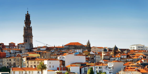 Colored facades and roofs of houses in Porto, with the bell tower of Torre dos Clerigos in the distance. Photo / 123RF