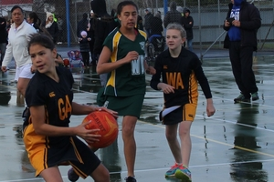 Year 7 netballer, goal attack Paton Paewai, left, secures the ball in the wet conditions, playing Hutt Valley in the Viking tournament.