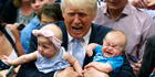 Republican presidential candidate Donald Trump holds Kellen Campbell of Denver, right, and Evelyn Keane, of Castle Rock, Colorado, during a campaign rally. Photo / AP