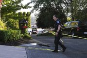 A police officer tapes off the scene of the shooting in the Chenault Beach neighbourhood of Mukilteo. Photo / AP