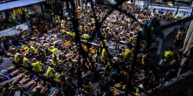 Inmates sleep on the ground of an open basketball court inside the Quezon City jail at night in Manila. Photo / Getty Images