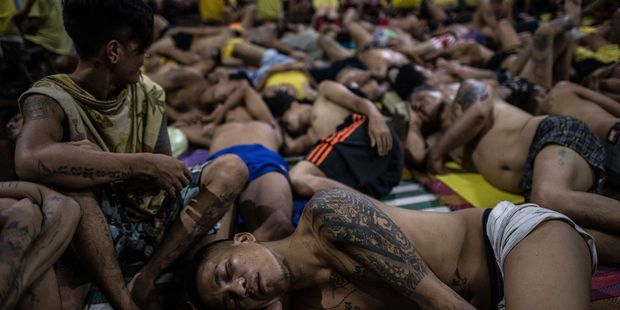 In this photo taken on July 21, 2016 inmates sleep on the ground inside the Quezon City jail at night in Manila. Photo / Getty Images