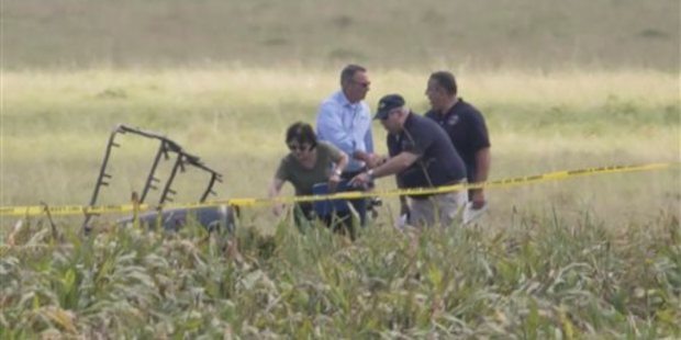 The partial frame of a hot air balloon is visible above a crop field as investigators comb the wreckage of the crash. Photo / AP