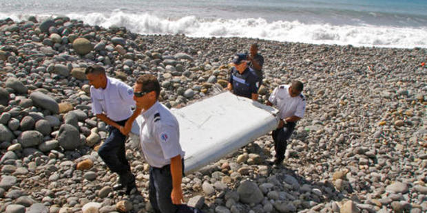 In this July 29, 2015 photo, French police officers carry a piece of debris, the first trace of Malaysia Airlines Flight 370, in Saint-Andre, Reunion Island. Photo / AP