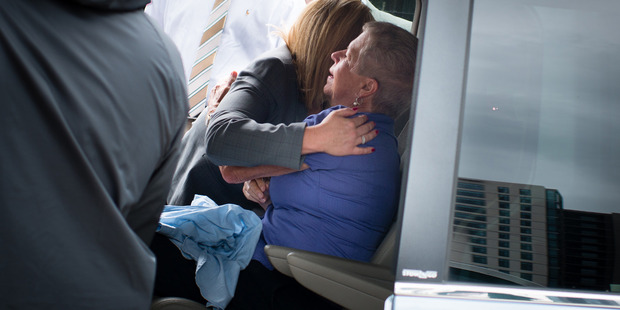 Mary Lyon, mother of Sheila Lyon and Katherine Lyon, gets a hug as she leaves a news conference. Photo / Washington Post