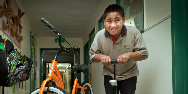 WHEELY GOOD: Fatui Tonga, 9, helps pump up the tyres of the donated bikes to Gate Pa school. PHOTO/Andrew Warner.