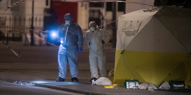 Police officers search the scene where Darlene Horton was stabbed in the back. Photo / AP