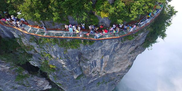 Loading Tourists take in the views from the glass-bottomed Panlong (meaning coiling dragon) Cliff skywalk, which sits some 300m above the valley floor in China's Zhangjiajie National Forest Park. Photo / Getty Images