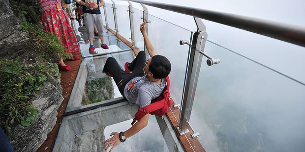 A tourist poses for a photo on a glass-bottomed skywalk on the new skywalk. Photo / Getty Images