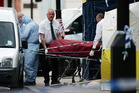 A body is removed from the scene in Russell Square in central London, after the knife attack yesterday. Photo / AP
