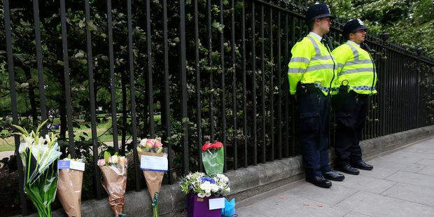Floral tributes rest against railings at Russell Square. Photo / AP