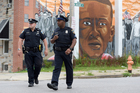 Baltimore police walk near a mural depicting Freddie Gray after prosecutors dropped remaining charges against the three Baltimore police officers who were still awaiting trial. Photo / AP