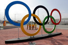 Volunteers stand near a set of Olympic Rings at Olympic Park in Rio de Janeiro. Photo / AP